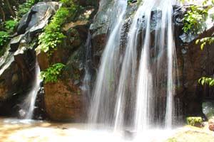 流れ落ちる滝に光が差し込む様子の写真