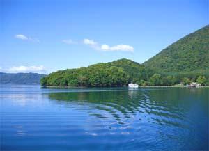青い空が映る水面と山の写真