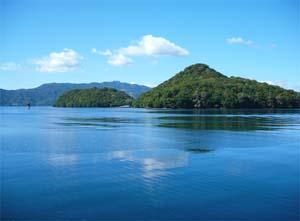 青く染まった湖の水面と山の写真