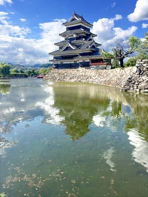 お堀の水面に映る松本城の写真