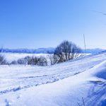雪の先に見える雲海と山々の写真