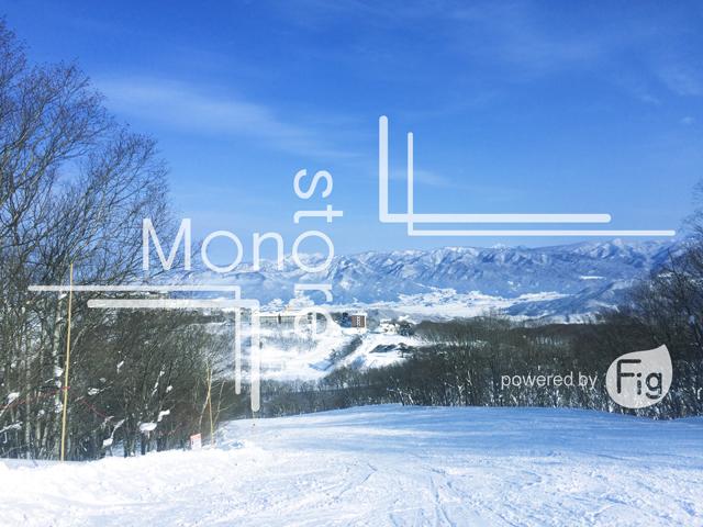 スキー場と雪の積もった山々と青空の写真