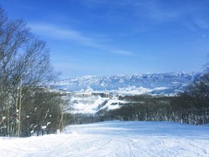 スキー場と雪の積もった山々と青空の写真[Photo10244]